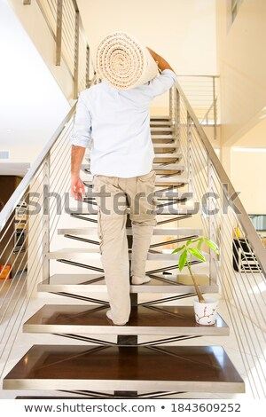 A man holding a rug in his new home Stock photo © IS2