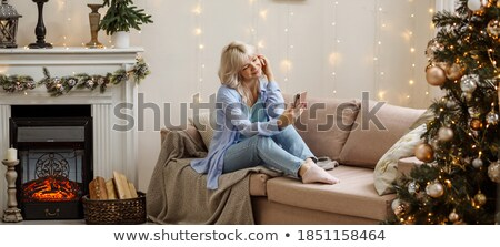 Woman next to a fir-tree, smiling Stock photo © IS2