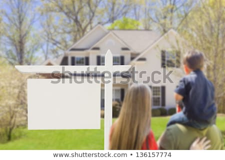 Caucasian Couple Facing Front of Sold Real Estate Sign and House Stock photo © feverpitch