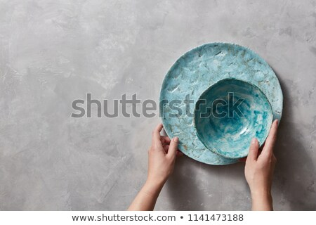 Vintage painted glazed plates dishes on gray concrete table with free space ror text. Girl hold hand Stock photo © artjazz