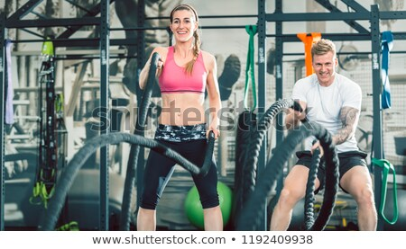two beautiful and strong women waving battle ropes during functional training stock photo © kzenon