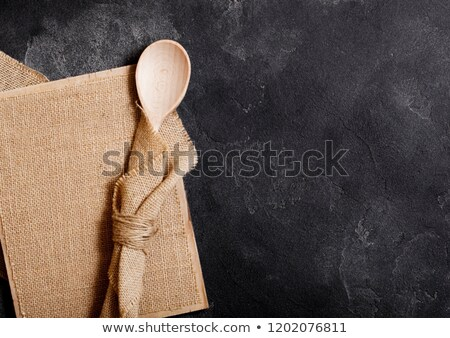Vintage kitchen wooden utensils with linen board on black stone table background. Top view.  Stock photo © DenisMArt