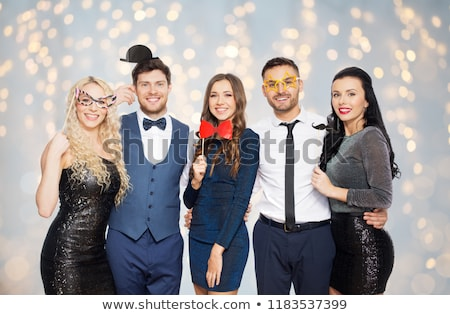 happy friends with party props posing over lights stock photo © dolgachov
