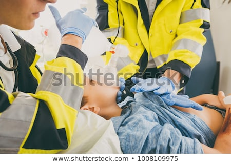 Emergency doctor giving cardiac massage for reanimation in ambulance Stock photo © Kzenon