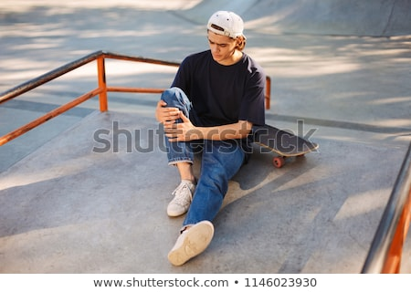 Young skater guy sit in the park with skateboard. Stock photo © deandrobot