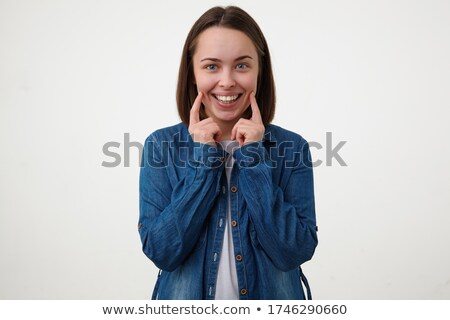 Portrait of pretty brunette woman looking at camera, posing and emotion smiling Wearing jean shorts, stock photo © studiolucky