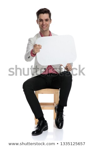 seated happy man pointing his finger to blank speech bubble stock photo © feedough