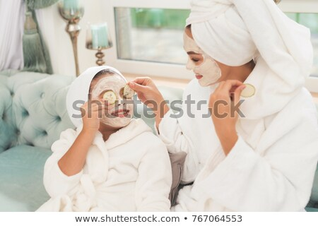 photo of young woman wrapped in towel applying face mask at the stock photo © deandrobot