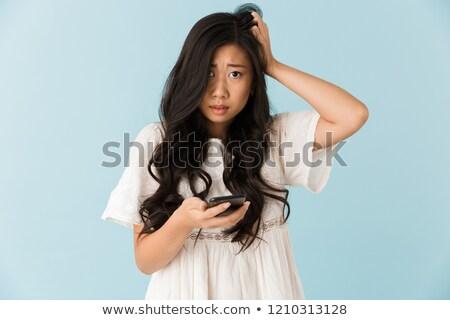 Paura asian bella donna isolato blu cellulare Foto d'archivio © deandrobot