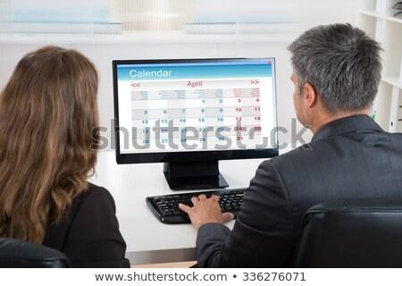 Kettő üzletemberek néz naptár asztali számítógép asztal Stock fotó © AndreyPopov