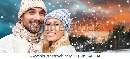 smiling man in hat and scarf over winter forest Stock photo © dolgachov