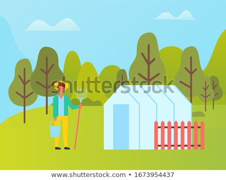 Farmer with Fork near Greenhouse with Red Fence Stock photo © robuart