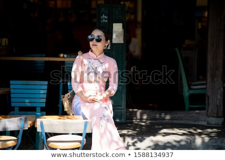 Young woman tourist and Vietnamese hats. Travel around Vietnam concept stock photo © galitskaya