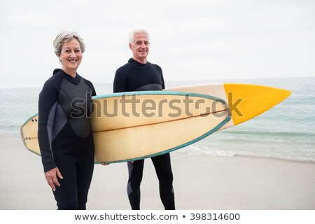 front view of senior couple with surfboard standing on beach and looking at camera on a sunny day stock photo © wavebreak_media