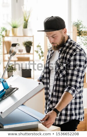 Serious craftsman holding stripe with decor while printing it on new pet collar Stock photo © pressmaster
