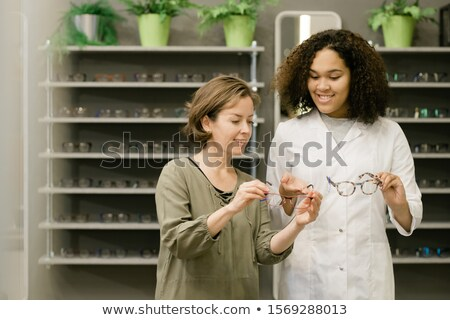 Young client of optics shop holding eyeglasses while listening to consultant Stock photo © pressmaster