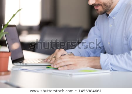 Concentrated young male accountant writes in notebook, makes business analysis and counts figures fo Stock photo © vkstudio