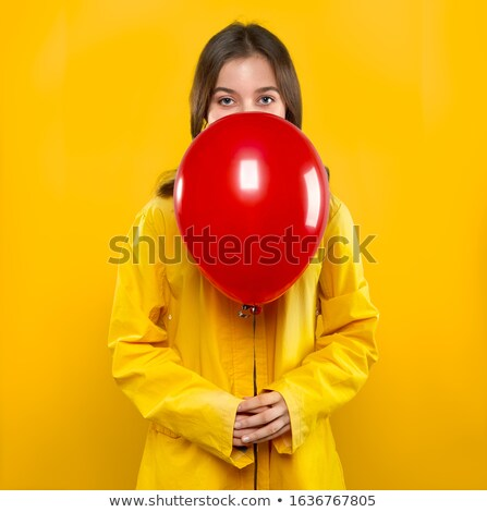 Pretty girl in yellow coat with red air balloon in hands Stock photo © LoopAll