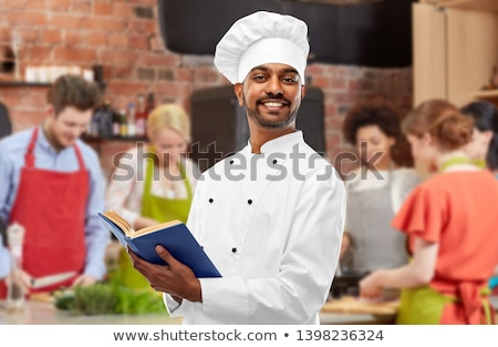 male indian chef reading cookbook at cooking class Stock photo © dolgachov
