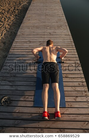 Young healthy man doing push-ups with special equipment Stock photo © deandrobot