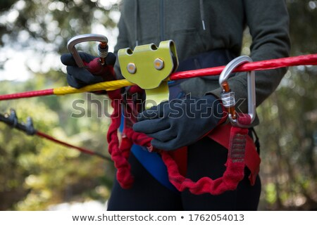 Woman adjusting her harness on zip line cable in the forest on a sunny day Stock photo © wavebreak_media