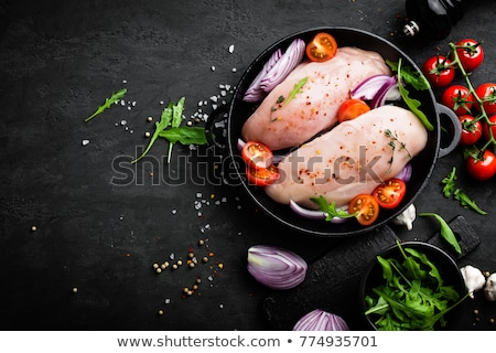 Fresh raw chicken meat, fillet marinated with spices, onion and tomatoes on black background. Top vi Stock photo © yelenayemchuk