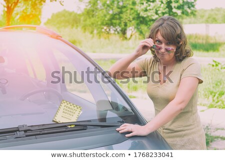 woman looking at ticket fine for parking violation on car stock photo © andreypopov