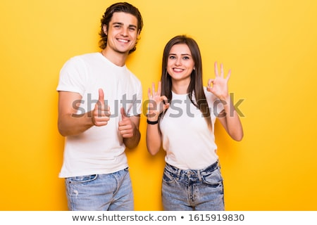 Happy cute young woman posing isolated over yellow background holding gift box present. Stock photo © deandrobot