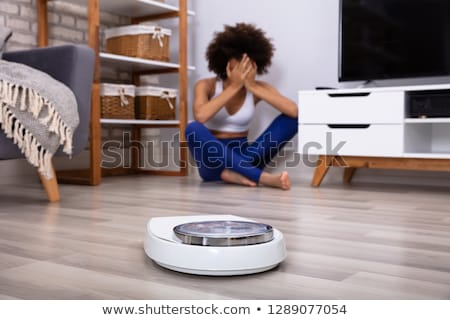 weighing scale in front of crying young woman on floor stock photo © andreypopov