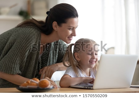 mother with little girl using laptop in the kitchen stock photo © dashapetrenko