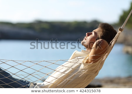 Young Man Relaxing On Hammock At Beach Stock photo © AndreyPopov