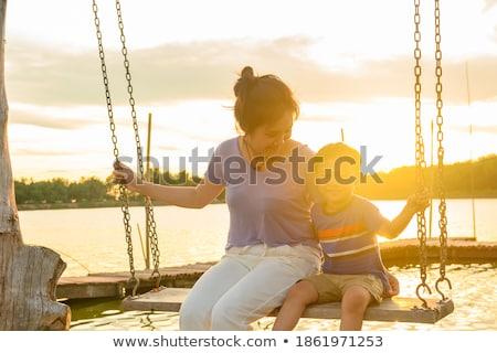 S'asseoir Swing mer rive coucher du soleil Photo stock © galitskaya