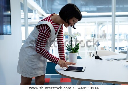 side view of pretty mixed race female executive using digital tablet in modern office with business stock photo © wavebreak_media