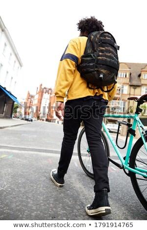 hipster man parking fixed gear bike on city street Stock photo © dolgachov
