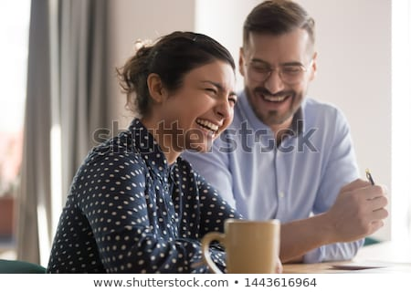 Two young cheerful multicultural women looking at man in new eyeglasses Stock photo © pressmaster