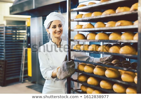 Stock photo: Baker rolling trays with fresh bread thru the bakery