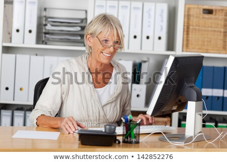 Positive woman works in office, sits at desktop, concentrated into monitor, drinks fresh milkshake,  Stock photo © vkstudio