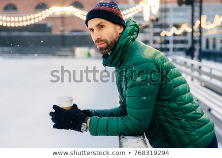 Thoughtful man with thick beard leans at hence, holds takeaway c Stock photo © vkstudio