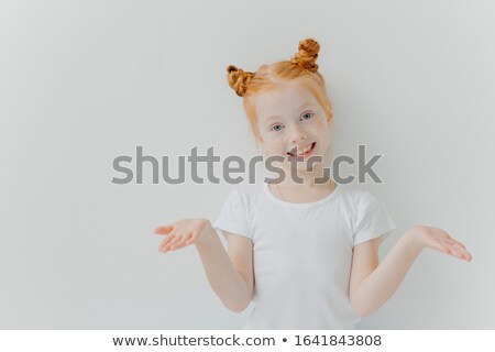 Pretty small female kid with double foxy buns spreads palms sideways, looks happily at camera, has g Stock photo © vkstudio