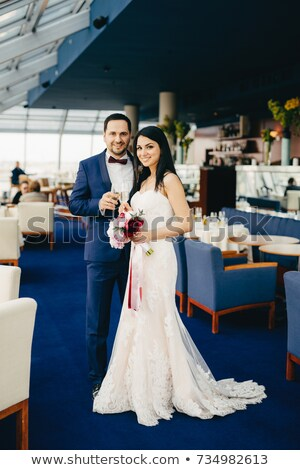 Vertical portrait of good looking female bride and bridegroom hold glasses with champagne, celebrate Stock photo © vkstudio