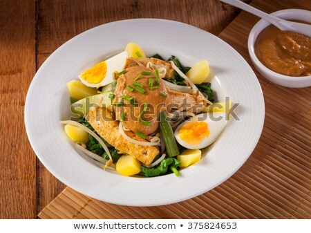 Gado-gado Indonesian salad served with peanut sauce. Ingredients: tofu, spinach, string beans, soy s Stock photo © galitskaya
