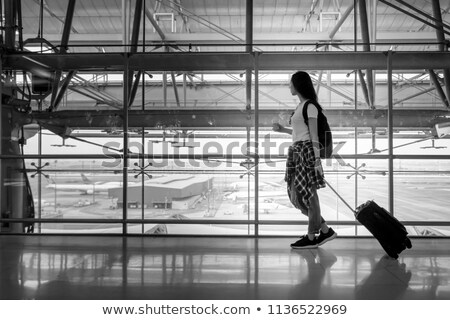Silhouette of woman waiting at airport terminal for flight boarding. Businesswoman traveling looking Stock photo © Maridav