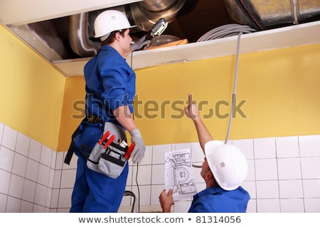 Stockfoto: Two Technicians Checking The Air Conditioning In The Ceiling