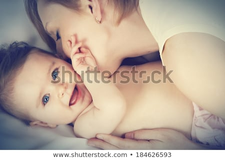 Close-up of a young mother holding the hand of her baby lying on his cradle at home stock photo © wavebreak_media
