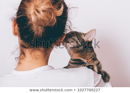 young woman holding beautiful tabby cat relaxed on gray backgro stock photo © hasloo