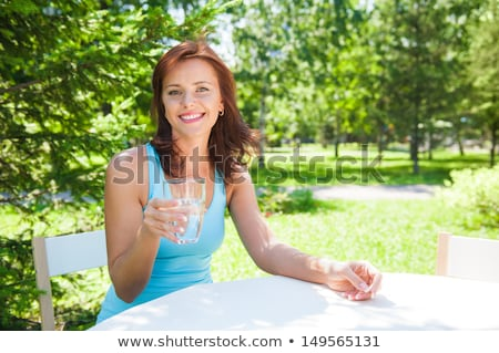 Portrait of young beautiful woman drinking water on picnic Stock photo © HASLOO
