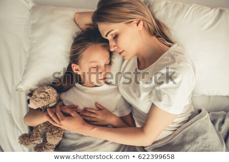 young beautiful woman sleeping on bed with her teddy bear stock photo © andreypopov