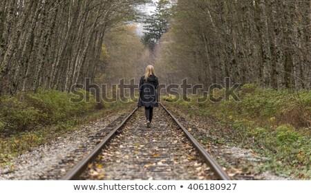 Genç kadın yürüyüş aşağı demiryolu izlemek uzak Stok fotoğraf © smithore