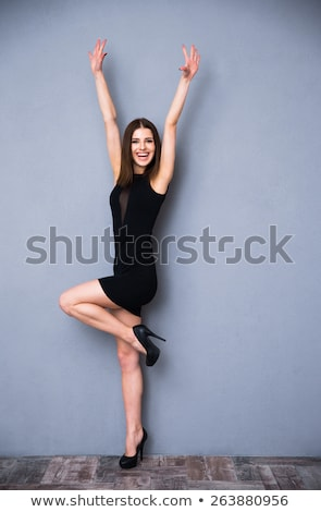 full length portrait of a beautiful woman in black dress on gray background stock photo © deandrobot