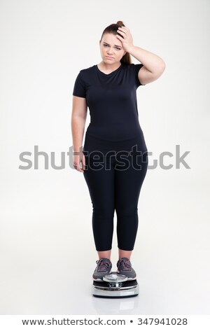 Sad thick woman standing on weighing machine Stock photo © deandrobot